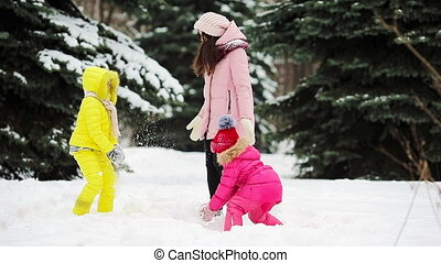 Happy family enjoy winter snowy day and playing snowballs -...