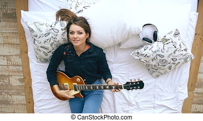 Portrait of attractive young girl learning to play electric...