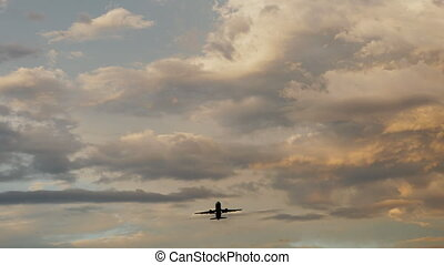 Passenger airplane taking off at sunset against the...