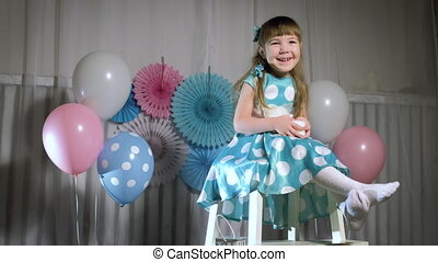 Beautiful little girl smiling. Balloons. Large number two -...