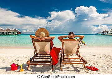 Couple in loungers on beach at Maldives - Couple in loungers...
