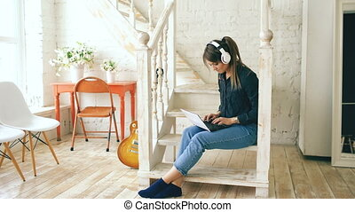 Beautiful woman with headphones relaxing with laptop while sitting on stairs in living room at home