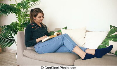 Happy teen girl resting on sofa at the living Room while reading her favorite novel book at home