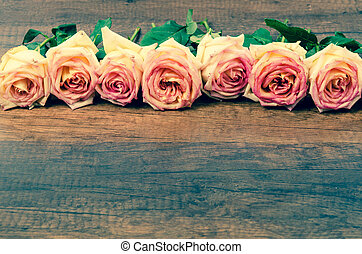 Pink roses on wooden. - Pink roses on wooden background with...