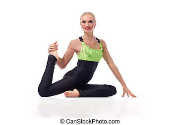 Gorgeous young woman practicing yoga sitting on the floor -...