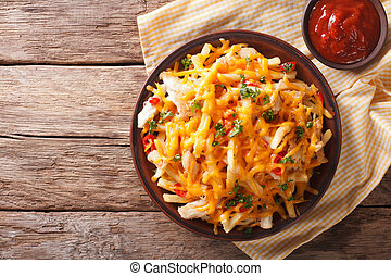 Spicy fast food: French fries with cheddar cheese, chili and chicken fillet close-up. horizontal top view