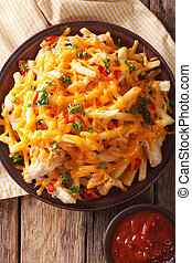 Spicy fast food: French fries with cheddar cheese, chili and chicken fillet close-up. vertical top view