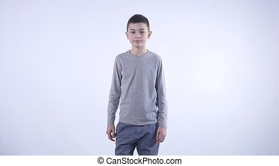 Portrait of confused clueless boy against white background....