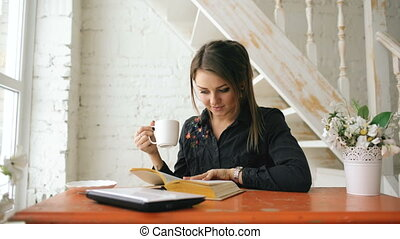 Young beautiful woman student sitting with laptop and reading book at cafe indoors