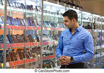 The young man, choosing camera in the department of household appliances in the shopping center supermarket