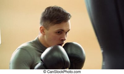 Young boxer practicing with a punching bag, close-up