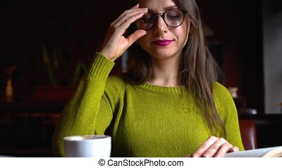 Woman reading the book and drinking coffee in a cafe -...