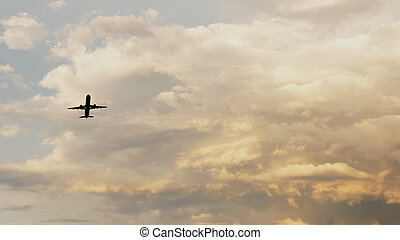 Passenger airplane taking off at sunset against the background of a very beautiful clouds.