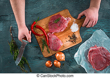 Butcher cutting pork meat on kitchen on wooden table on blue...