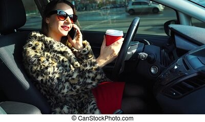 Beautiful woman in a fur coat using a smartphone and...