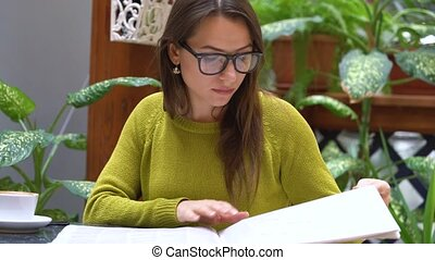 Woman reading newspaper and drinking coffee in a cafe -...