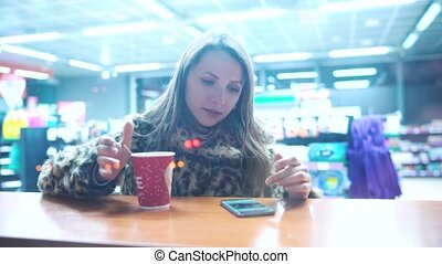 Woman using app on smartphone and drinking coffee in cafe in...