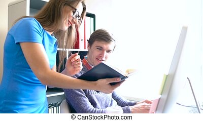 Beautiful young woman and man working from home office -...