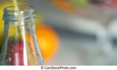 Orange juice pouring into a glass bottle - Concept of tasty...
