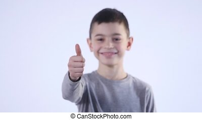 smiling boy holding his thumb up isolated on the white background