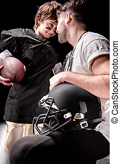 smiling man and boy with rugby ball looking at each other