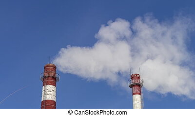 Air Pollution From Industrial Enterprises. Large pipes throwing smoke in the sky. environmental protection, the steam from the heating system boiler