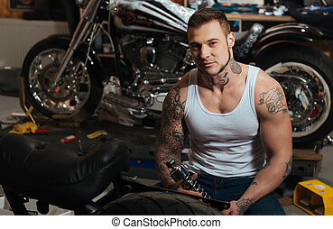 Delighted muscular man holding spare part