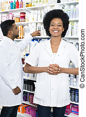 Pharmacist With Hands Clasped Smiling While Colleague...