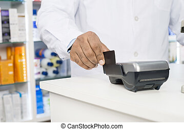 Midsection Of Chemist Swiping Credit Card On Reader -...