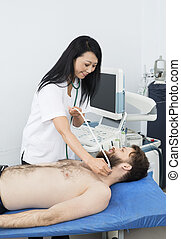 Doctor Performing Thyroid Ultrasound Test On Patient -...