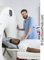 Doctor About To Start CT Scan On Male Patient - Portrait of...