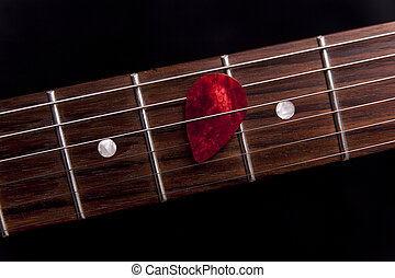 Red guitar pick on the fingerboard