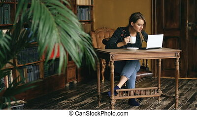 Smiling student girl working on laptop and drink coffee in university library indoors