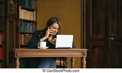 Pretty young student girl talking on the mobile phone while studying in the library indoors