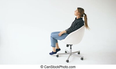 Happy young girl ride white modern office chair and have fun on white background