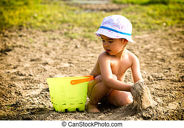 Cute little girl playing with sand