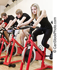Group of people having spinning class with a girl in focus