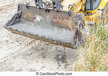 Excavator is carry bucket filled with fresh concrete -...