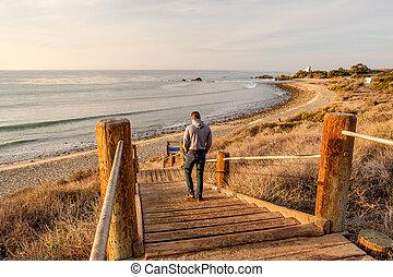 Man walking at boardwalk to beach, Malibu. - Man walking at...
