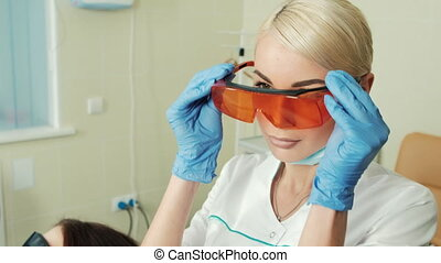 Young beautiful dentist putting uv protection on before work...