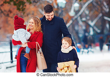 happy family walking on winter street at holidays
