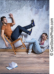 Woman kicking toppling chair on which is sitting shocked man