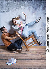 Woman on toppling chair - Scared woman on toppling chair and...