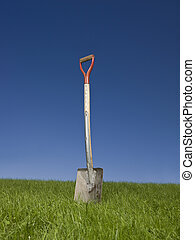 Shovel in green grass against a blue sky