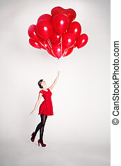 Carefree Young Woman with Red Balloons