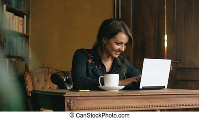 Slow motion of smiling student girl working on laptop in university library indoors