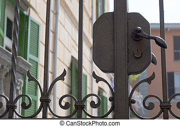 Wrought iron fence, view on traditional houses, Italy
