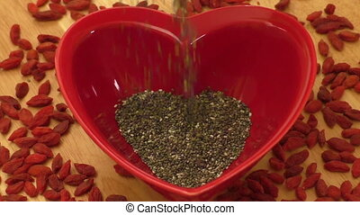 Chia seeds in heart shaped ceramic bowl and dried goji...