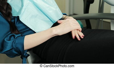 Patient is nervous sitting in chair in dental office during...