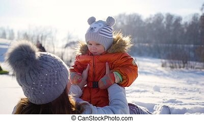 Girl plays with baby at sunny in winter time. Holding on hands